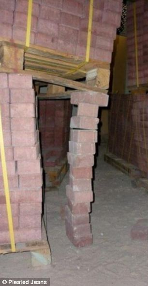 A pallet of bricks are propped up using a single column of bricks .