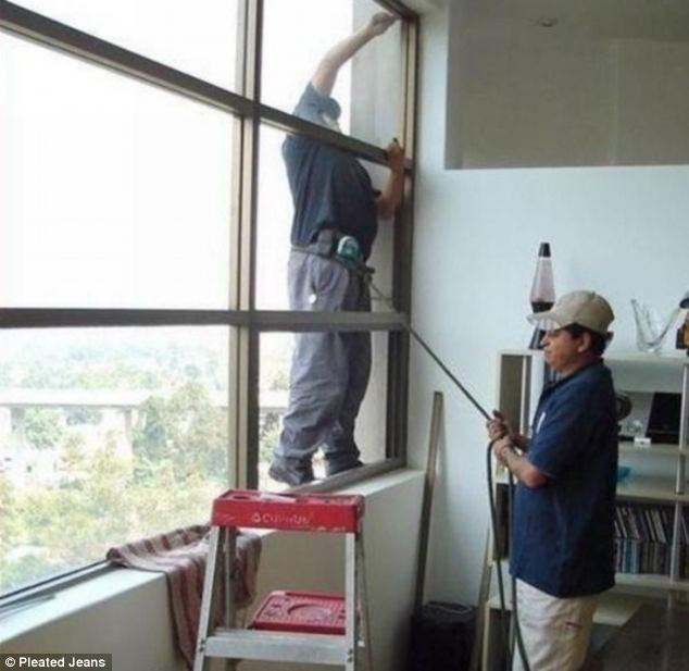 A man who is working on a window from the outside is held secure by his co-worker attaching a rope to his belt and holding on to it